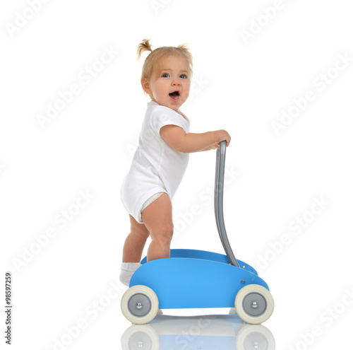 Photo  Cute smiling baby girl toddler with toy walker make first steps