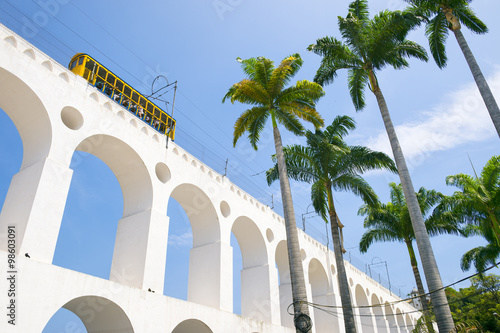 Bonde de Santa Teresa tram train drives along distinctive white arches of the landmark Arcos da Lapa Arches in Centro of Rio de Janeiro Brazil