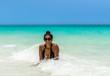 Kubanerin im Meer unter blauem Himmel am Strand von Kuba