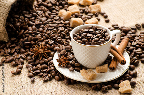 Photo  Coffee beans poured into the Cup and saucer and a bag of coffee