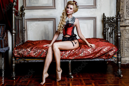 Blonde Woman in medieval corset  historic dress and lingerie  posing in bed Fototapeta