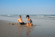 Thai brother and sister ages 8 and 6 have fun on the beach