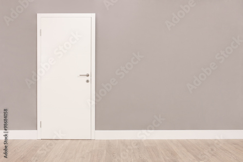 Fotomural  White door in an empty room