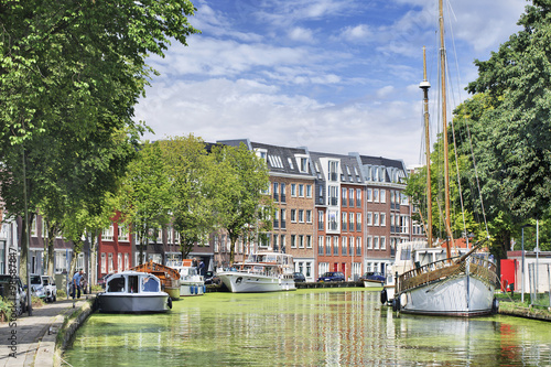 Spoed Foto op Canvas Kanaal Green canal with moored yachts and apartment buildings, Gouda, Netherlands.