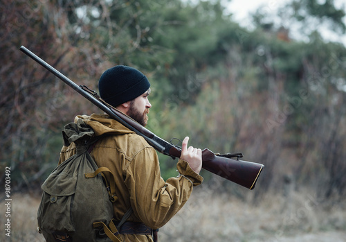 Fotografie, Obraz  brutal hunter, bearded man in warm hat with a gun in his hand, a knife a backpac
