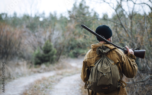 Fotografía  brutal hunter, bearded man in warm hat with a gun in his hand, a knife a backpac