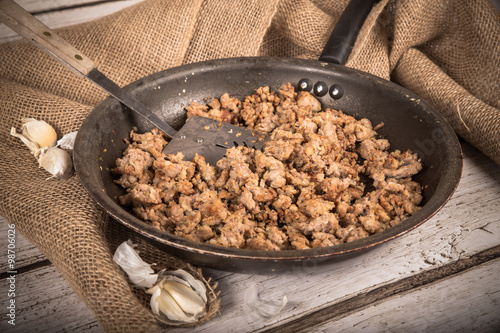 фотография  Cooking Ground sausage meat in frying pan with garlic and burlap background