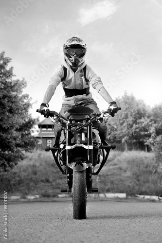 Foto op Canvas Motorsport Wanna try? Black and white soft smudged focus portrait of a stuntman sitting on his motorbike ready to entertain the viewers