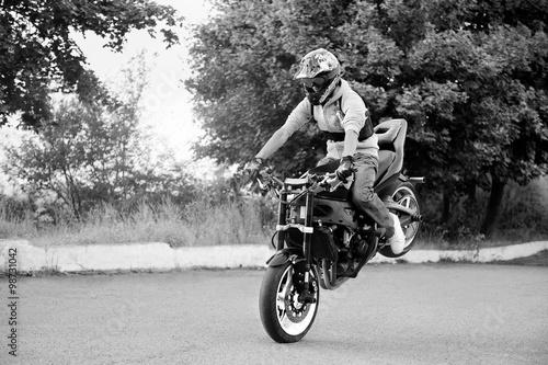 Foto op Plexiglas Motorsport Extreme hobby. Talented risky stuntmen riding his motorbike on the road black and white shot soft smudged focus