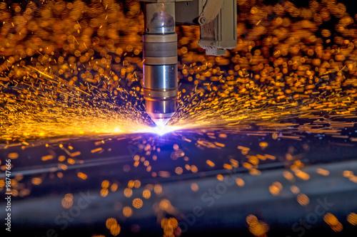 Fotografía  CNC Plasma torch cutting steelplate with orange bokeh sparks