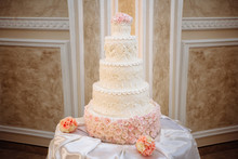 Big Sweet White Wedding Cake With Pink Roses On A White Table