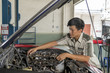 Young mechanic repairing car in service center