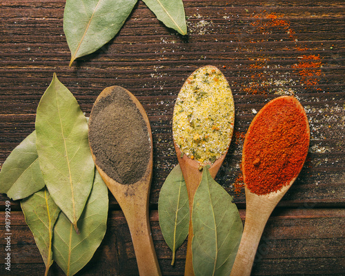 Spices in wooden spoons with laurel leaves Canvas Print