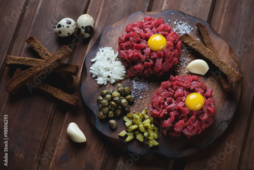 Photo  Beef tartar with yolk, capers, pickles, onion and breadsticks