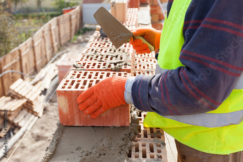 Fotografía  Construction mason worker bricklayer installing red brick with trowel putty knif