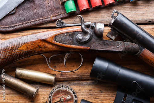 Spoed Foto op Canvas Jacht The hunting rifle, cartridge belt,binoculars on a wooden table