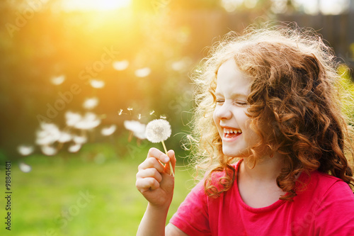 Fotografie, Obraz  Little curly girl blowing dandelion and laughing.