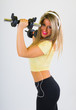 Mujer joven rubia con ropa deportiva escuchando música con cascos y smartphone y haciendo ejercicio con pesas