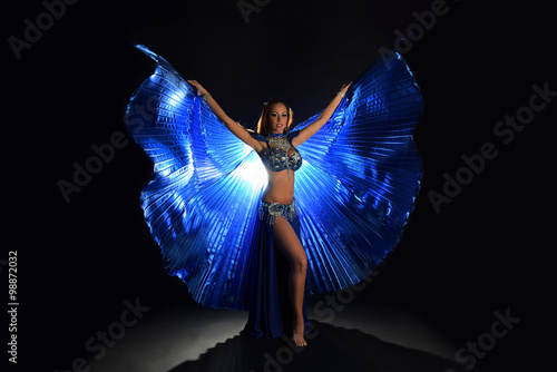 Cadres-photo bureau Carnaval Belly dancer woman in blue costume with wings on dark background