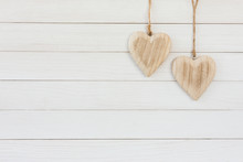 Two Wooden Hearts On White Wooden Background. Copy Space