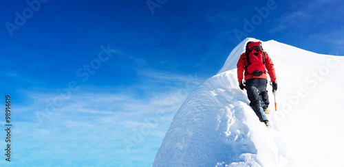 Alpinisme Mountaineer arrive to the summit of a snowy peak. Concepts: determination, courage, effort, self-realization. Clear sky, sunny day, winter season. Large copy-space on the left. European Alps, Europe.