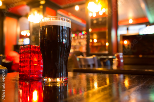 Fotografía  Glass of dark beer with candle in pub setting