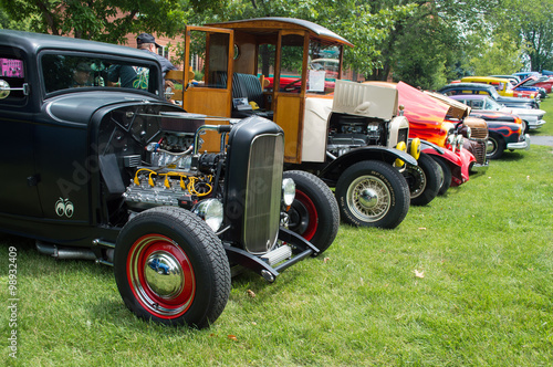Poster Vintage voitures Vintage hot rods and rat rod trucks and show car front ends. A row of sweet hot rods at a car show restored front ends with headlights exposed engines and grilles. Trucks and cars at a car show.