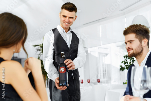 Romantic Dinner. Sommelier Presenting Best Wine To Happy Couple In Love. People Having Date In Gourmet Restaurant. Celebrating Anniversary Or Valentine's Day. Romance, Relationship. Alcoholic Drinks.
