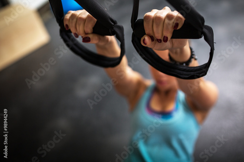 Zdjęcie XXL Młoda kobieta na siłowni działa na jej abs na trx