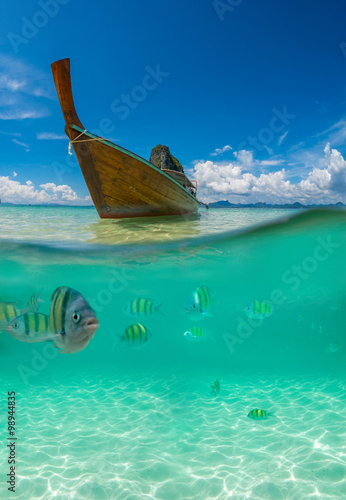 Photo  Underwater picture with fish and traditional longtail boat in Ma