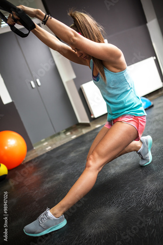 Fotografia  Young female at the gym working on her abs on trx