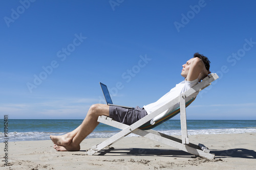 Foto op Aluminium Ontspanning Successful businessman resting on a tropical beach with laptop