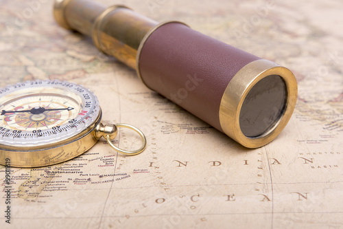 Fotografia  Old compass and old telescope on vintage map world explorer concept