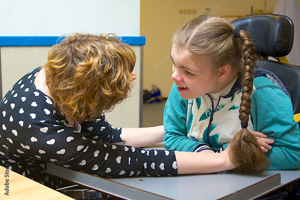 Fototapety, obrazy: Disability a disabled child having fun / Disability a disabled child smiling at the care assistant