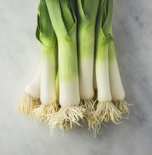 Bundle Of Fresh Leeks - Closeup Of Some Fresh Leeks With The White Bulb And Roots Displayed On A Gray Mottled Marble Cutting Surface