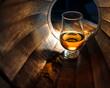 Leinwanddruck Bild - A glass of whiskey in oak barrels