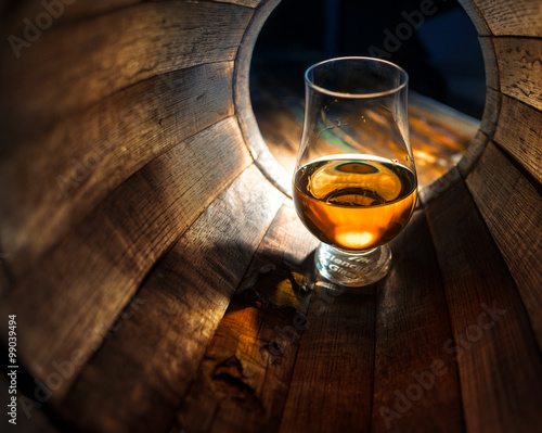 A glass of whiskey in oak barrels