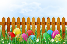 Easter Background With Easter Eggs In Grass And Wooden Fence