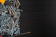 screws, bolts and screwdriver on wooden background