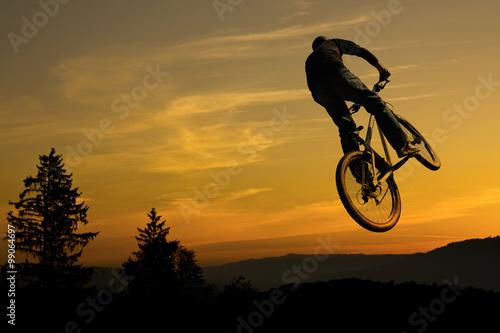 Mountain bike stunt against nice sunrise