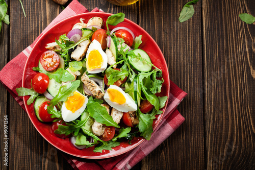 Fresh salad with chicken, tomatoes, eggs and arugula on plate