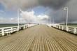 rain passing over a wooden, sea pier