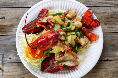 Photo  Steamed whole lobster and garnishes on white serving plate