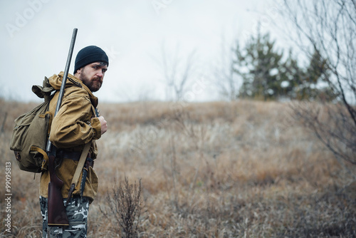 brutal hunter, bearded man in warm hat with a gun in his hand, a knife a backpac Canvas-taulu