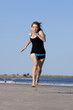 Woman running on the beach barefooted