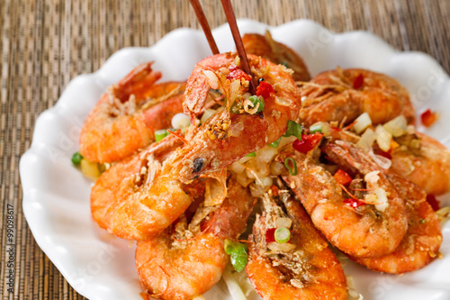 Photo  Fried bread coated shrimp and garnishes on white serving plate