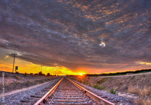 Sunset rays streak from below the cirrocumulus clouds over train tracks.