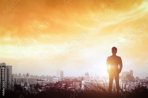 Obrazy na płótnie Canvas Silhouette of businessman to city way light the sunset.