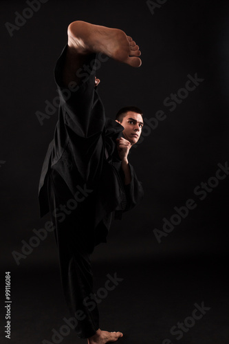 Studio portrait of young karate fighter kicking over black background Canvas Print