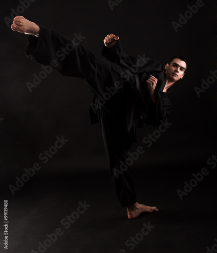 Printed kitchen splashbacks Martial arts Studio portrait of young karate fighter kicking over black background.